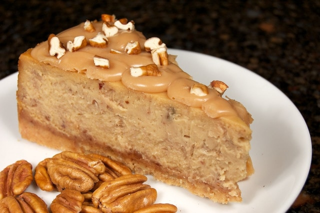A slice of Praline Cheesecake on a plate next to some pecans