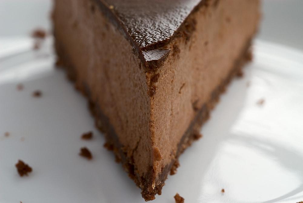 slice of Chocolate-Glazed Hazelnut Mousse Cake on a white plate
