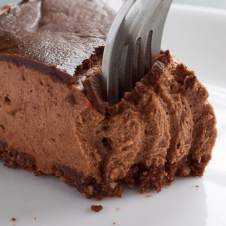 a fork digging into a slice of Chocolate-Glazed Hazelnut Mousse Cake