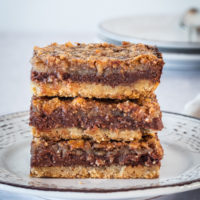 stack of chocolate pecan cheesecake bars on a plate