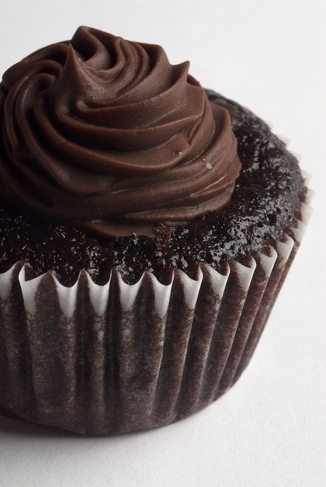 Chocolate Salted Caramel Mini Cupcakes feature a dark chocolate cupcake filled with salted caramel and topped with chocolate frosting and a sprinkle of salt.
