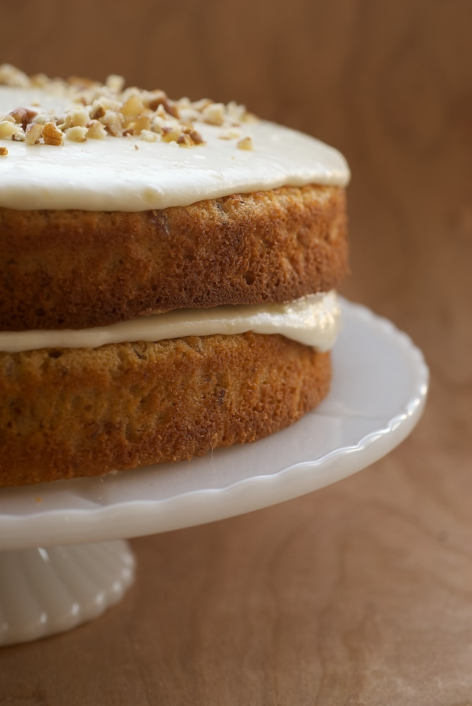 Pecan Layer Cake with Banana Icing on a milk glass cake stand