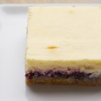 Lemon Blueberry Cheesecake Bars combine a nutty crust, blueberry preserves, and a lemony cheesecake for an irresistible dessert. - Bake or Break