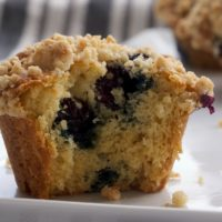 half of a Blueberry Crumb Muffin on a white plate