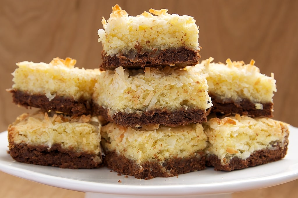 Coconut Bars with Chocolate Shortbread Crust stacked on a white serving pedestal