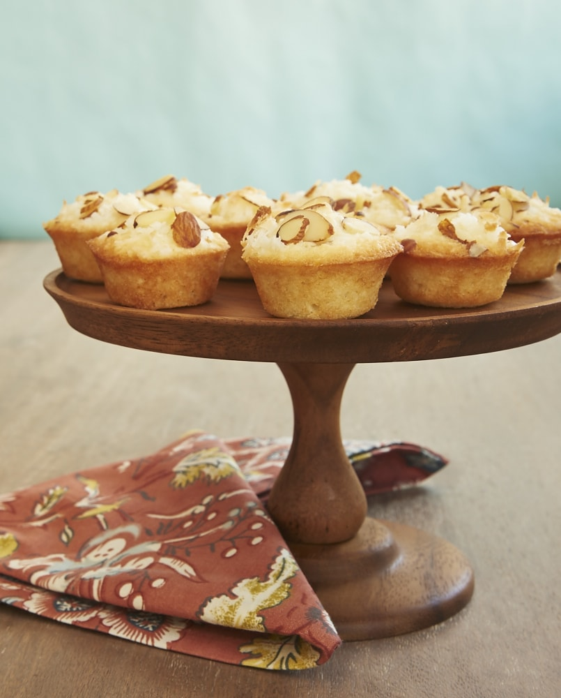 Mini Coconut Cakes on a small wooden cake stand