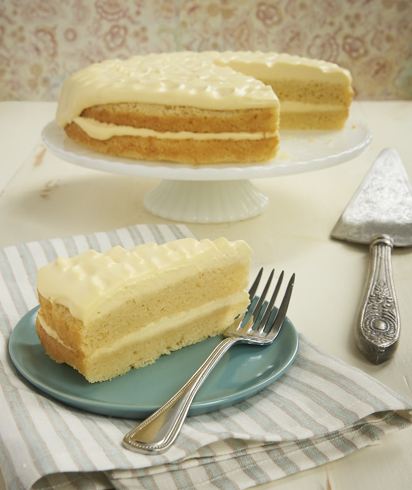 slice of Lemon Cream Cake on a green plate next to the cake on a white cake stand