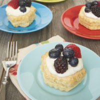 Berries and Cream Tartlets served on colorful plates