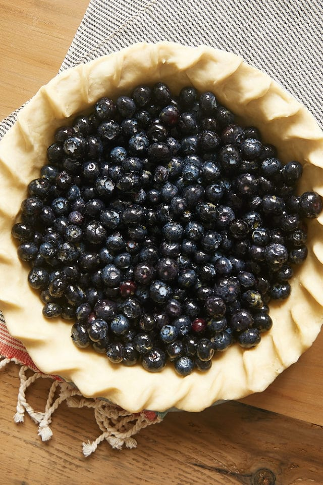 overhead view of blueberries in an unbaked pie crust
