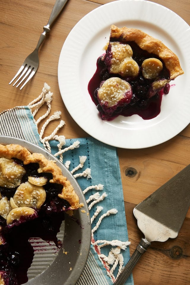 overhead view of a slice of Blueberry Ginger Pie on a white plate