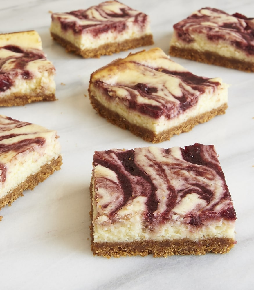 servings of Cherry Cheesecake Bars on a marble platter