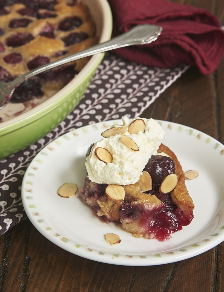 Brown Butter Cherry Cobbler topped with sweetened whipped cream and almonds
