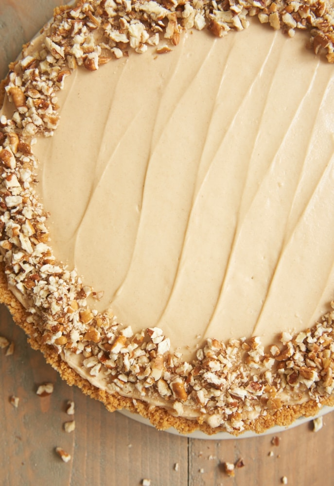 Brown Sugar Banana No-Bake Cheesecake topped with a ring of chopped pecans around the outside