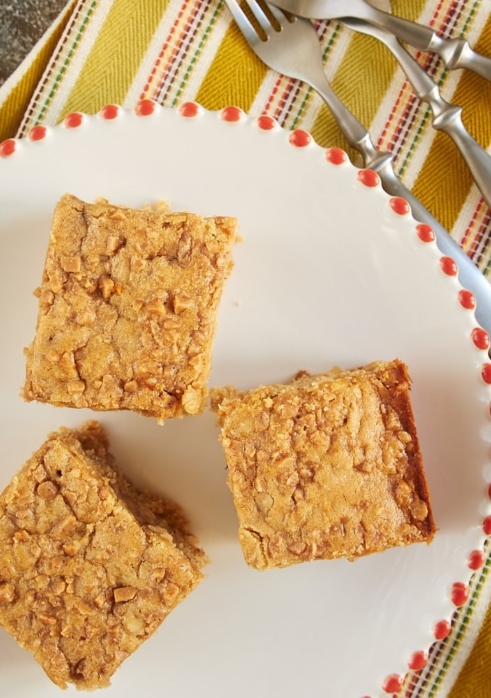 overhead view of Peanut Butter Toffee Snack Cake on a red-rimmed white plate