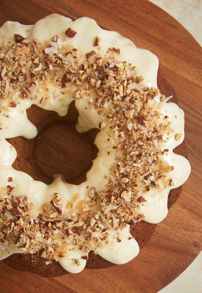 Italian Cream Bundt Cake topped with a cream cheese glaze, pecans, and toasted coconut