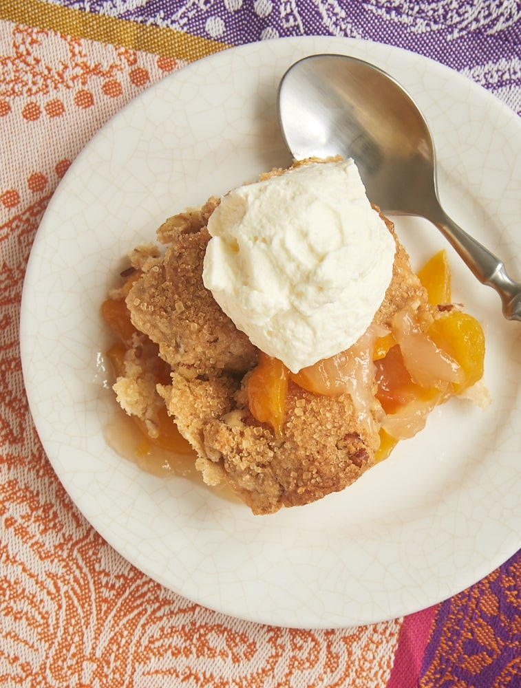 Ginger Pecan Peach Cobbler topped with sweetened whipped cream