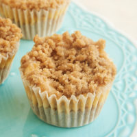 Mini Cinnamon Crumb Cheesecakes on a small blue pedestal