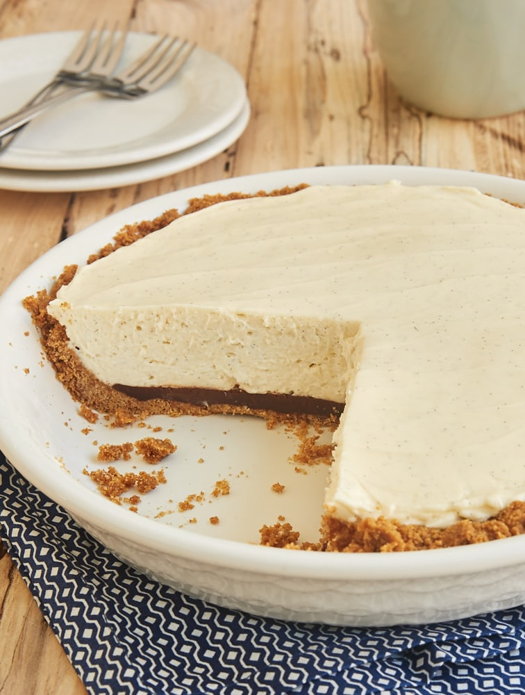 No-Bake Black Bottom Vanilla Bean Cheesecake in a white pie plate with two slices removed