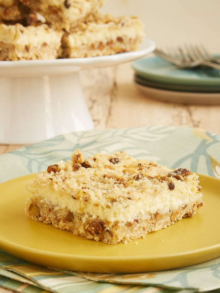 Lemon Pistachio Cheesecake Bars served on a yellow plate