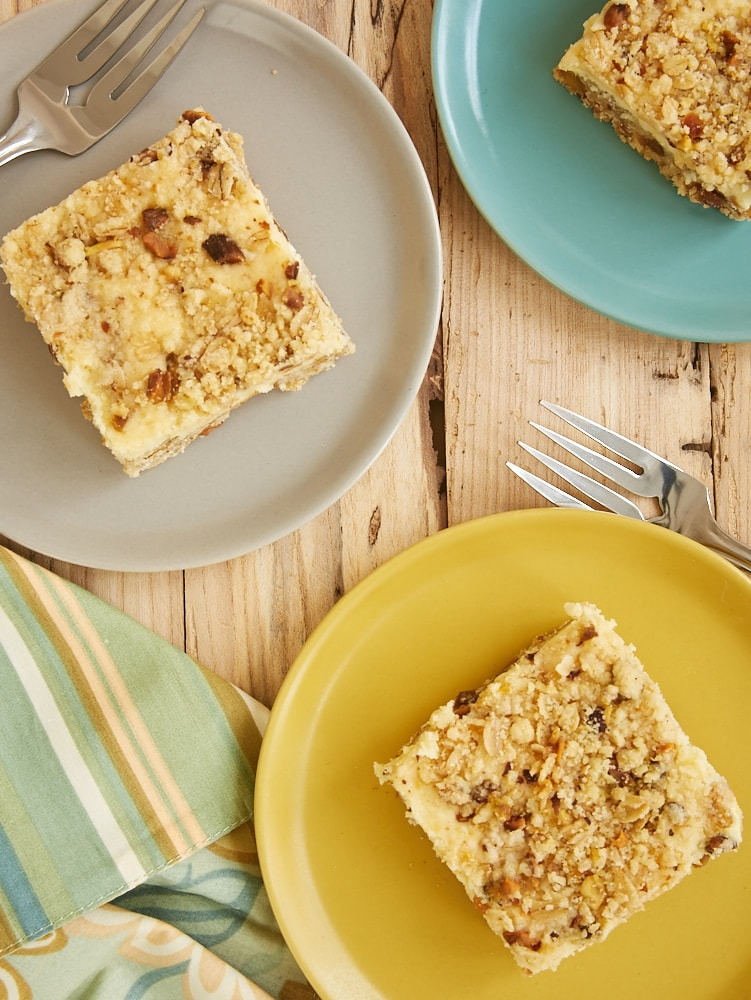 overhead view of Lemon Pistachio Cheesecake Bars on yellow, gray, and blue plates