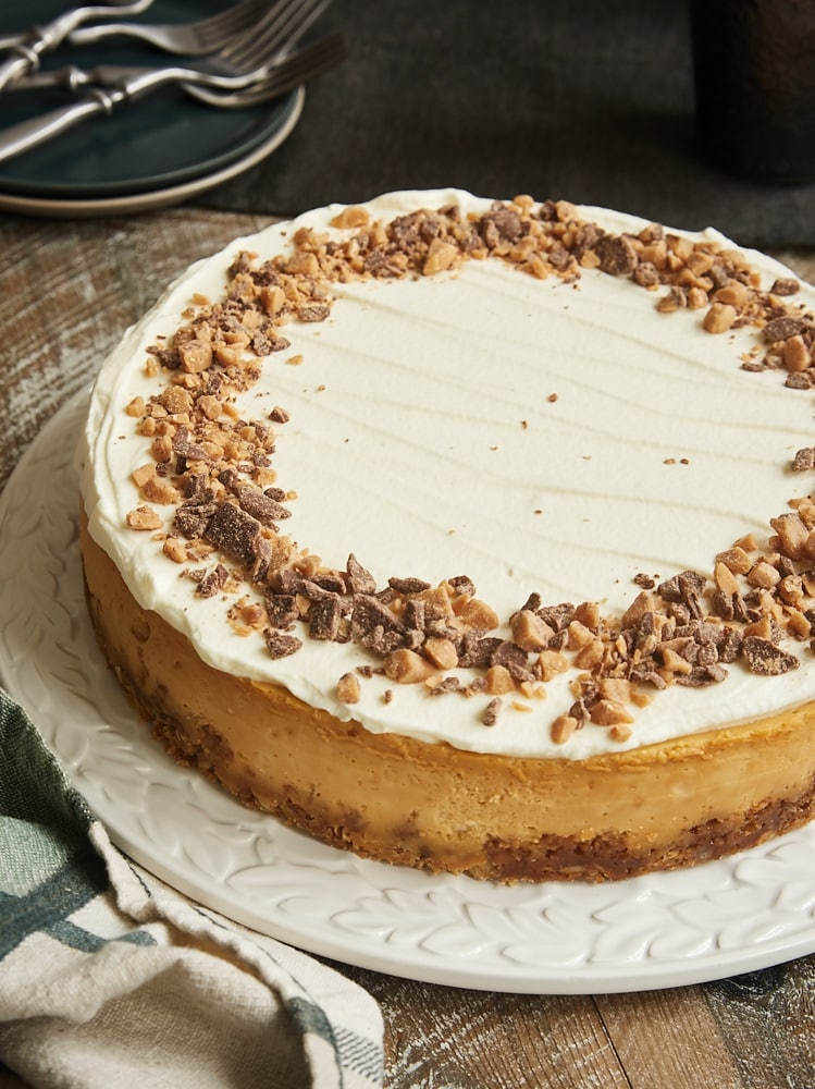 Brown Sugar Caramel Cheesecake with Oatmeal Cookie Crust on a round white serving tray