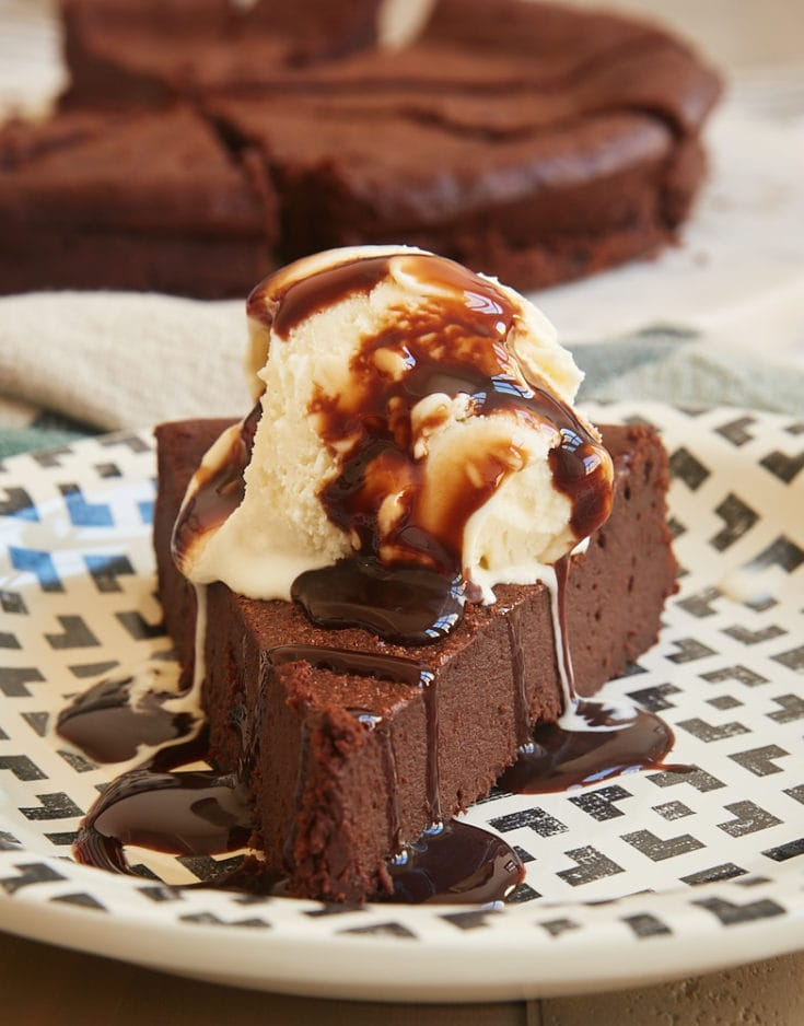 Slice of Easy Chocolate Torte topped with ice cream and chocolate sauce