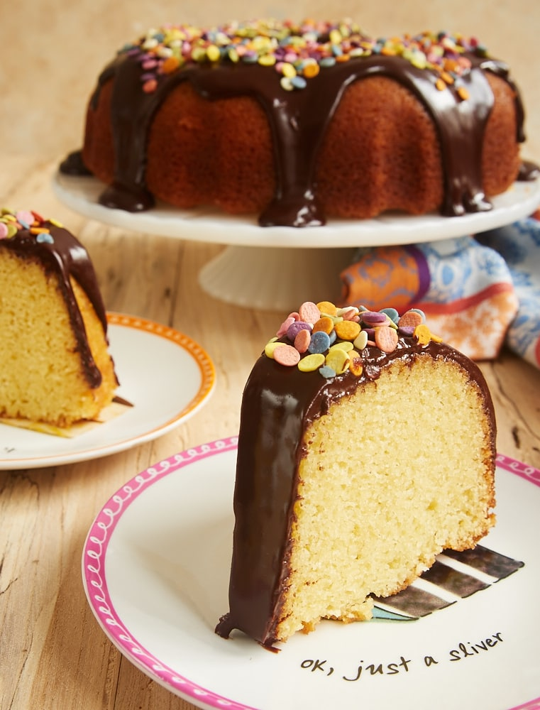 slice of Yellow Bundt Cake with Dark Chocolate Ganache on a pink-rimmed white plate