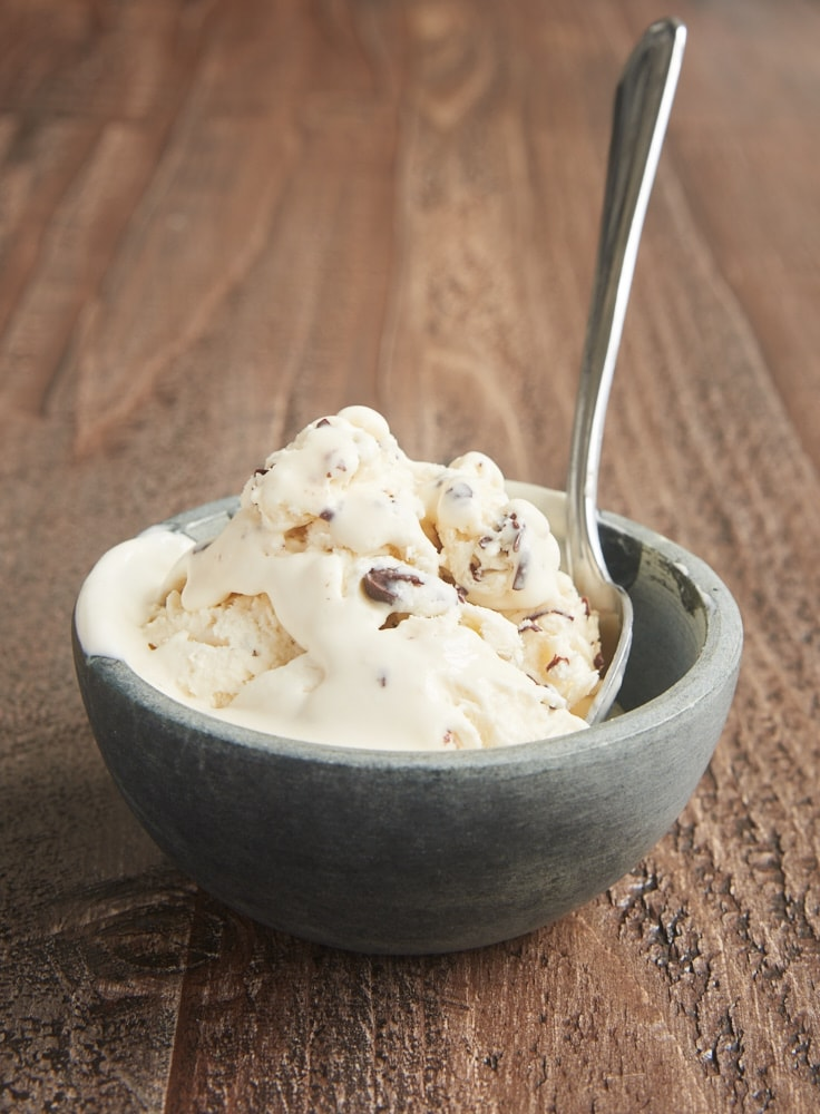 No-Churn Stracciatella Ice Cream in a gray bowl with a spoon sticking out of it