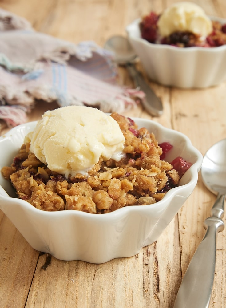 Skillet Berry Crumble served with ice cream in a white fluted bowl