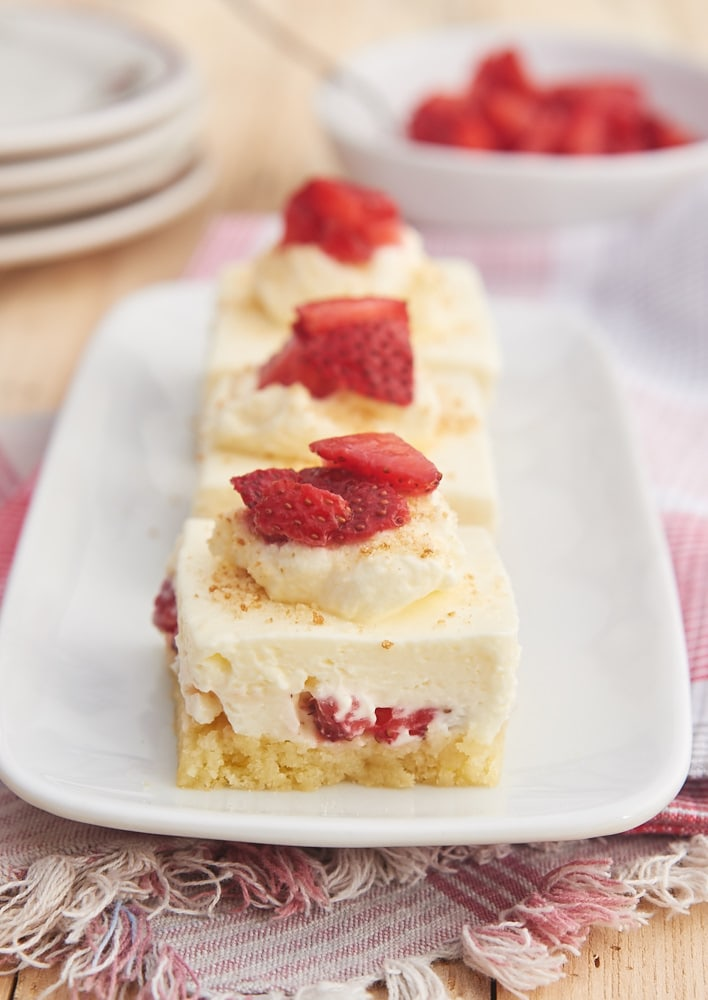 three slices of Strawberry Shortcake Cheesecake Bars lined up on a white rectangular plate