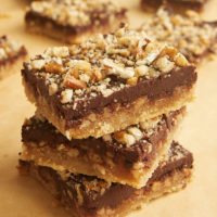 stack of Butter Pecan Turtle Bars on parchment paper