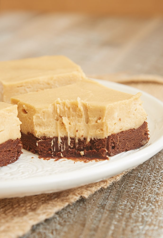 a slice of Brownie Bottom Peanut Butter Pie Bars with a bite missing
