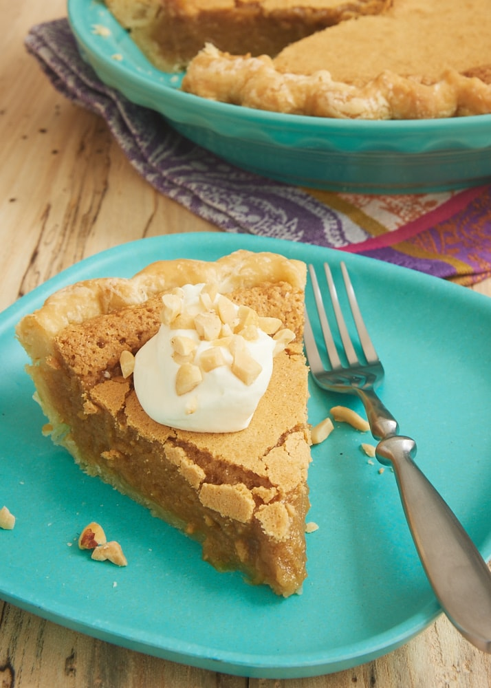Peanut Butter Chess Pie topped with sweetened whipped cream and served on a green plate