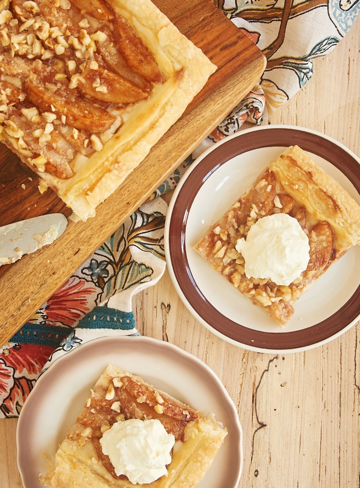 slices of Cream Cheese-Filled Pear Tart topped with sweetened whipped cream