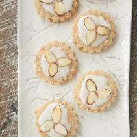 Almond Spice Cookies topped with a simple glaze and sliced almonds