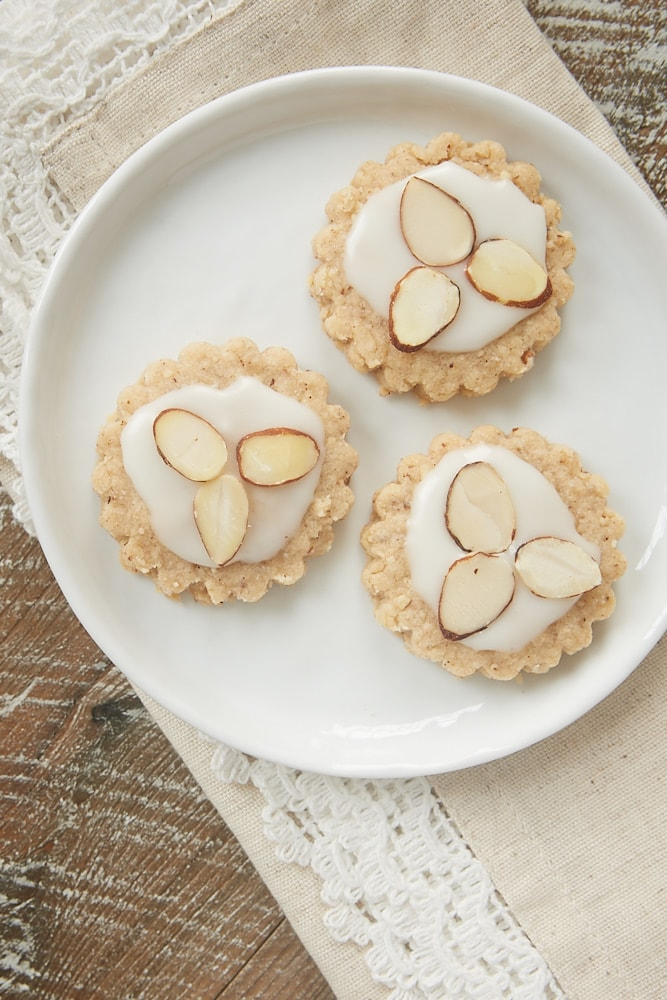 Almond Spice Cookies topped with a sweet glaze and sliced almonds