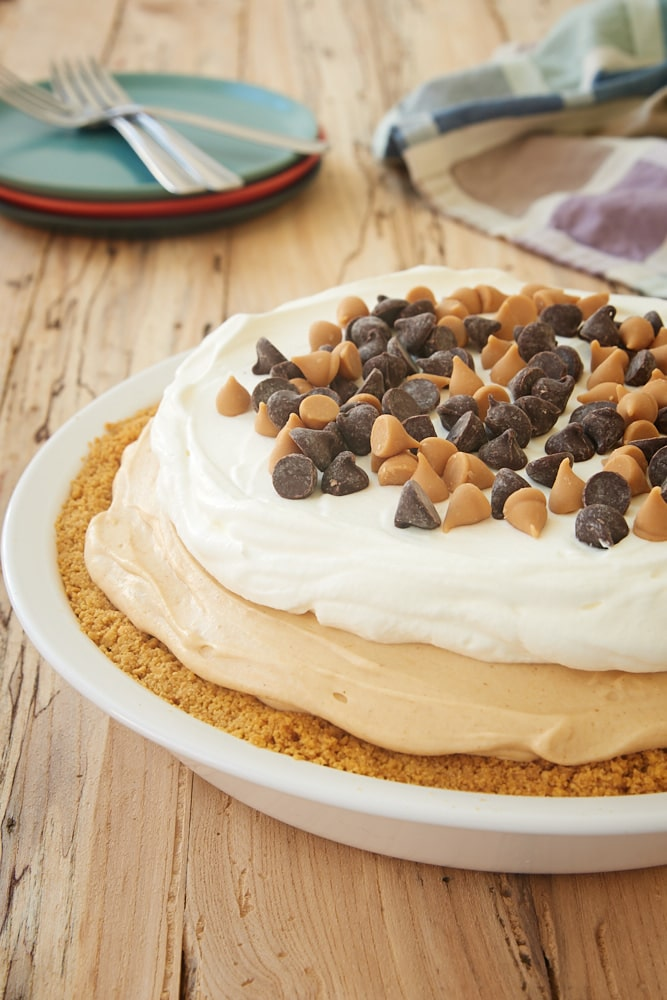 Black Bottom Peanut Butter Pie topped with sweetened whipped cream, peanut butter chips, and chocolate chips