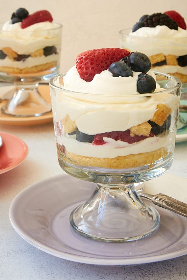 Berry Cheesecake Trifles topped with whipped cream and more berries