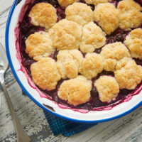 Blueberry Cobbler with Ginger Biscuits in a blue-rimmed white bowl