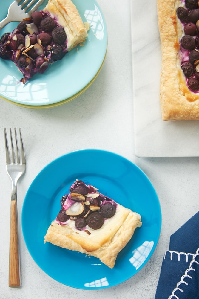 slices of Blueberry Cream Cheese Tart on blue plates