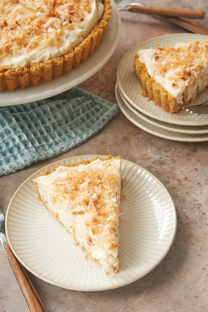 slices of No-Bake Coconut Cheesecake on white and beige plates