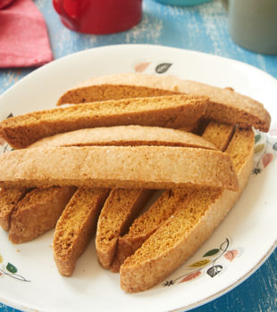 Vanilla Biscotti stacked on a white plate with a floral rim