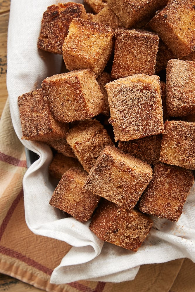 Cinnamon Sugar Pound Cake Bites piled in a towel-lined basket