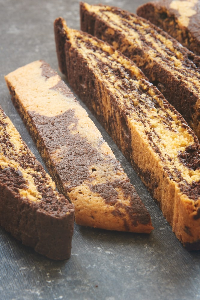 sliced Chocolate Vanilla Marbled Biscotti on a dark surface