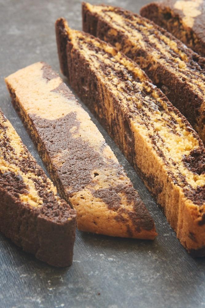 sliced Chocolate Vanilla Marbled Biscotti on a dark surface