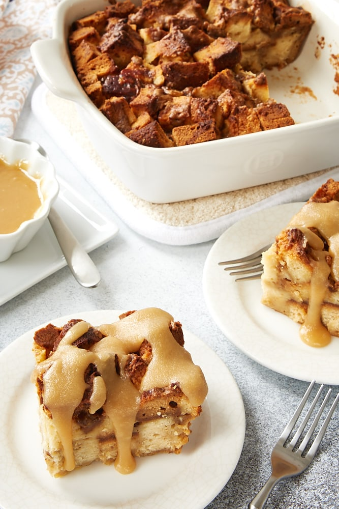 Cookie Butter Pound Cake Bread Pudding in a white ceramic baker with servings on white plates