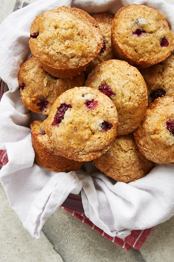 Cranberry Orange Muffins in a red dish lined with a white linen napkin