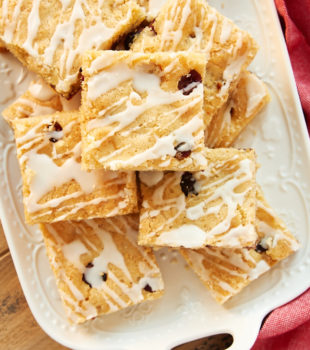 Cranberry White Chocolate Blondies stacked on a white tray