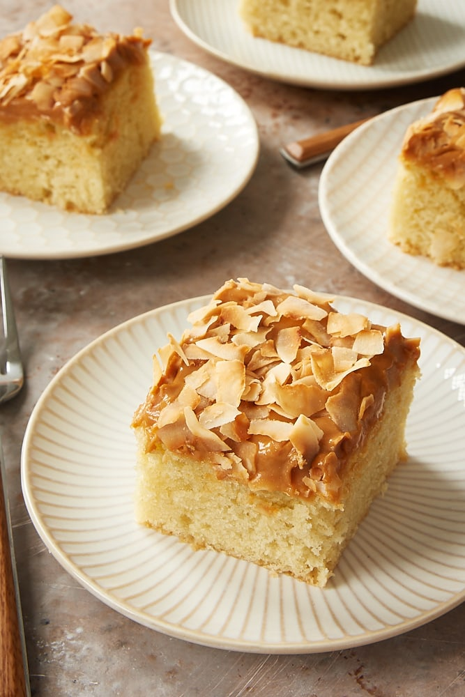slices of Coconut Cake with Dulce de Leche Frosting on white and beige plates