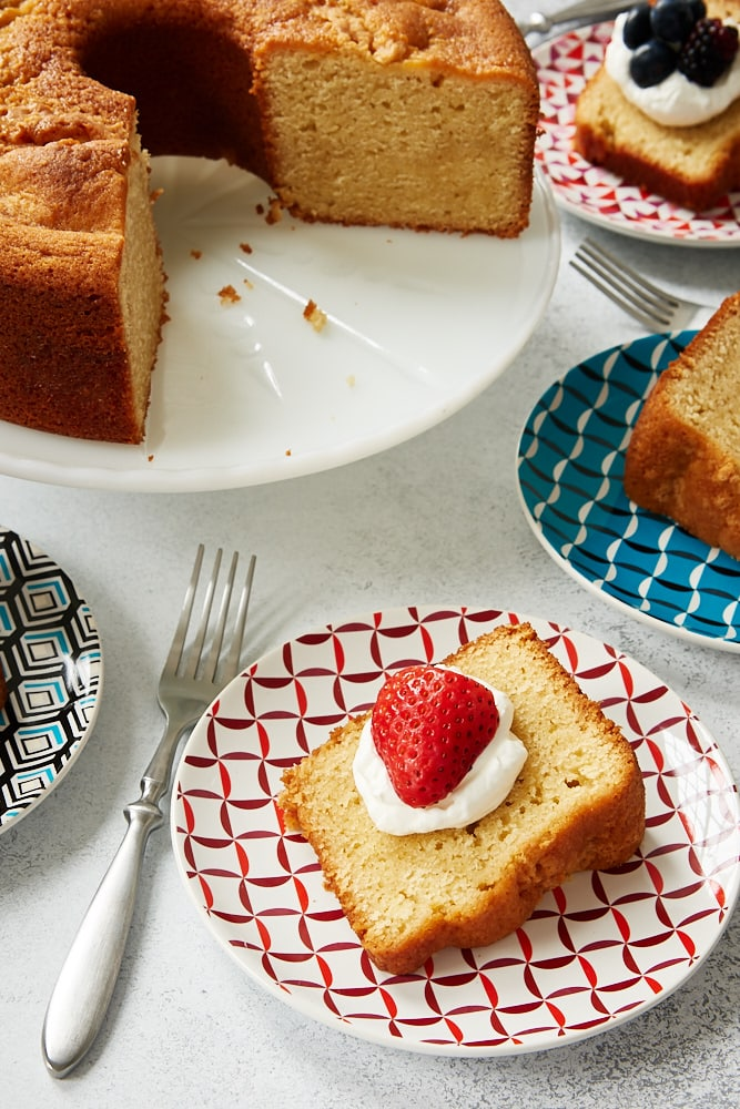 Sour Cream Pound Cake on a white cake stand with slices of cake around it